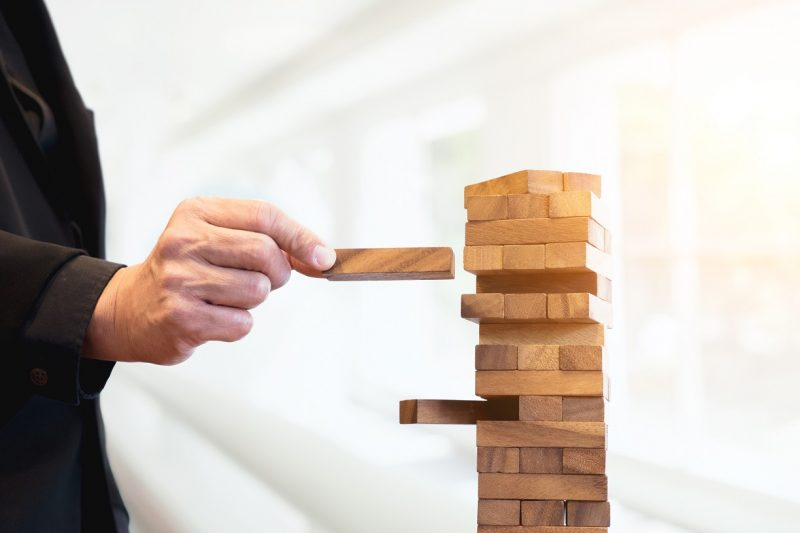 Planning, risk and strategy of project management in business, businessman and engineer gambling placing wooden block on a tower.Business and construction concept.
